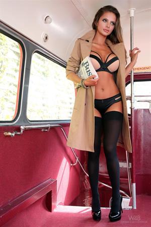 Dana Harem posing nude on a double decker bus