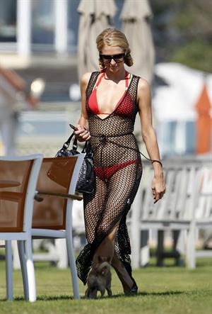 Paris Hilton at the beach in a skimpy red bikini and fishnet kaftan in Malibu.July 12, 2013