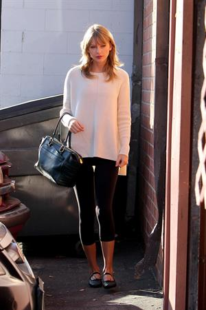 Taylor Swift wearing a white top and black pants in Los Angeles 10/28/13