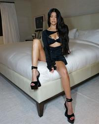 Kourtney Kardashian boobs showing nice cleavage with her big tits in a sexy revealing black outfit posing on her bed.